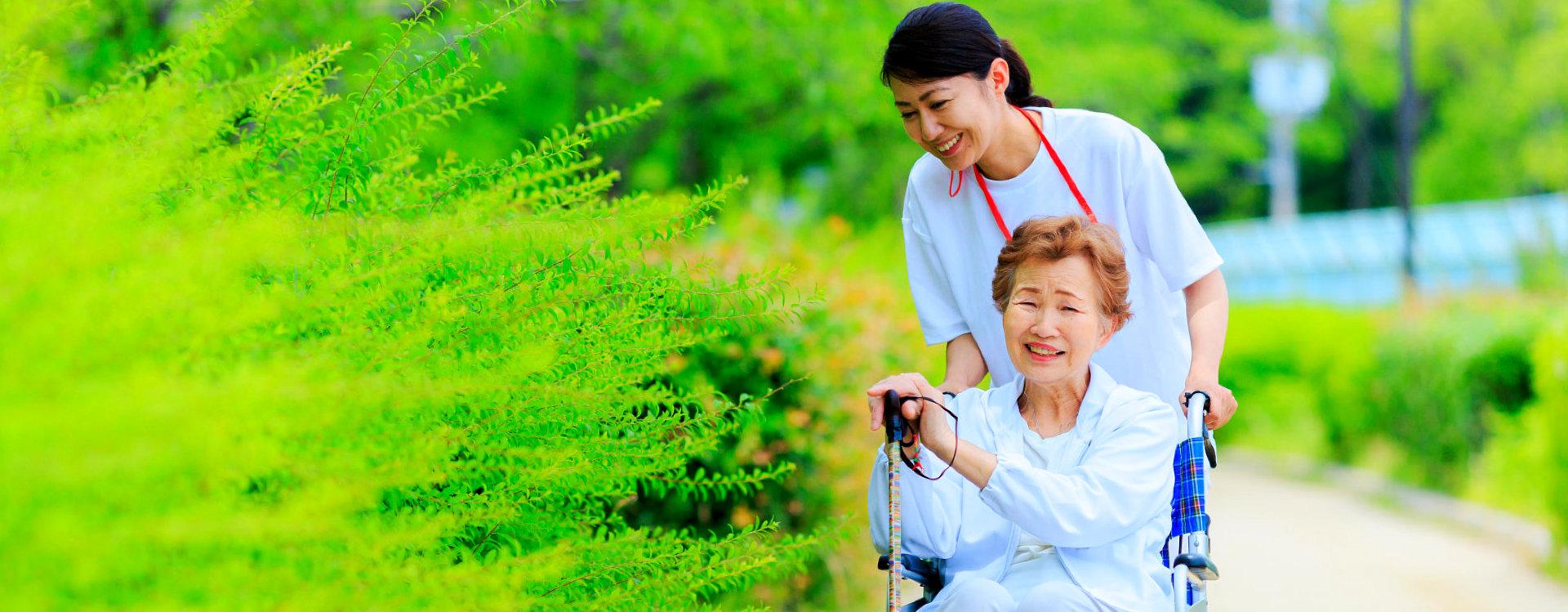 caregiver and senior woman outside senior home